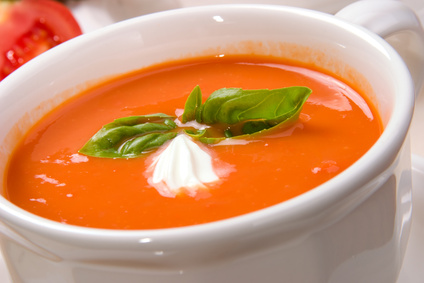 Closeup of bowl of delicious tomato soup garnished with cream and basil leaves